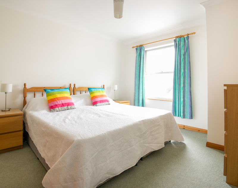 The colourful master bedroom with super king size bed that can convert to two singles in Slipway 15, a holiday rental in Rock, Cornwall.
