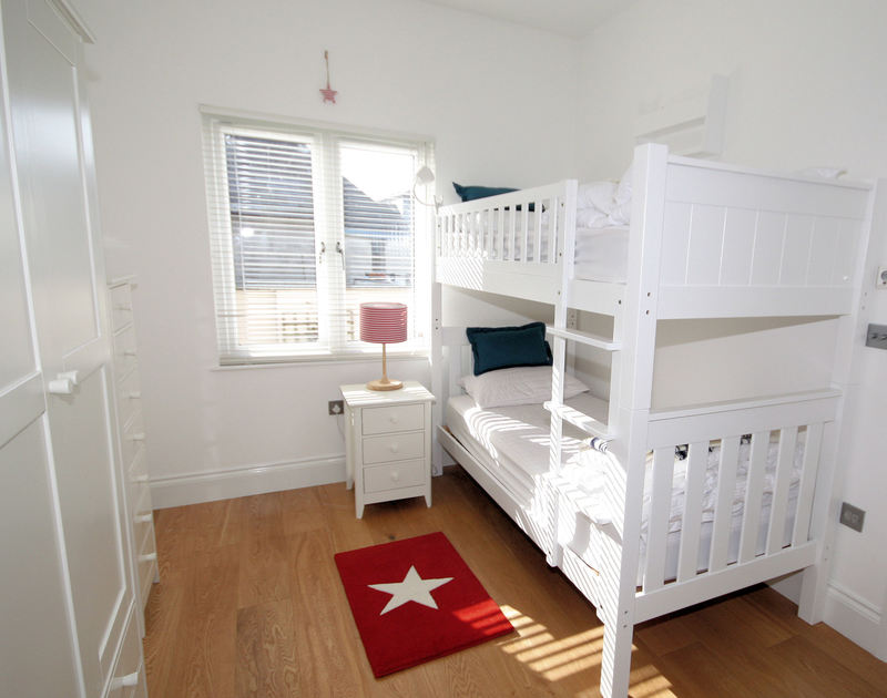 Bunk bedroom, stylishly furnished in white with window and fully tiled en-suite shower room in self catering holiday house The Saltbox in Port Isaac, North Cornwall.