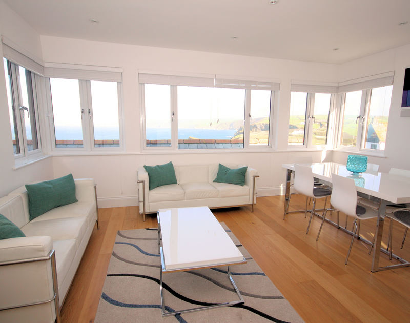 Tastefully furnished sitting/dining area and large windows with wonderful views along the North Cornwall coastline and out to sea from holiday rental The Saltbox in Port Isaac, Cornwall.