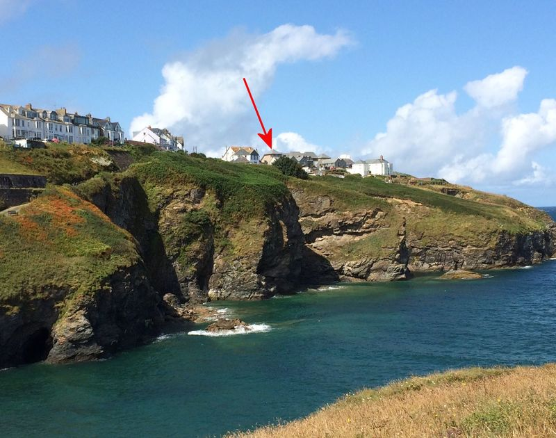 A red arrow pinpoints the location of self catering holiday house, The Saltbox, Port Isaac on the clifftop, with the rugged coastline below, overlooking the sea.