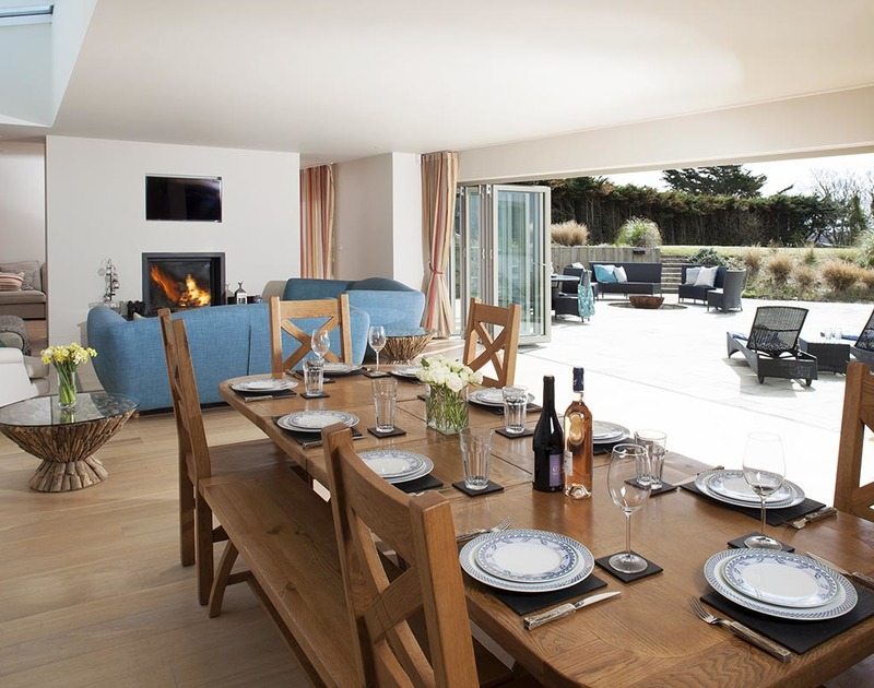 The open-plan dining room of Downalong, a luxury holiday house at Daymer Bay, Cornwall, with wide bi-fold doors opening onto the terrace.