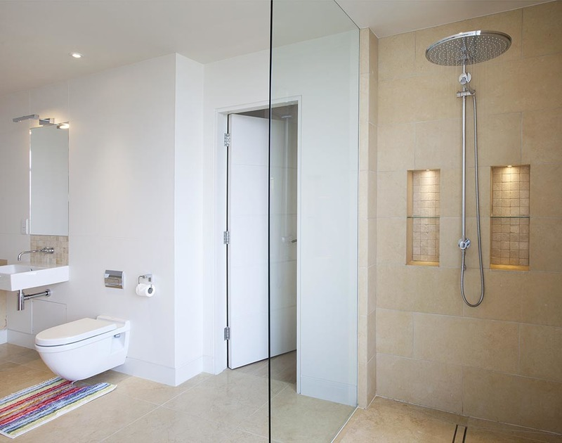 A spacious walk-in shower at Downalong, a luxury holiday rental at Daymer Bay, Cornwall, with its huge shower head.