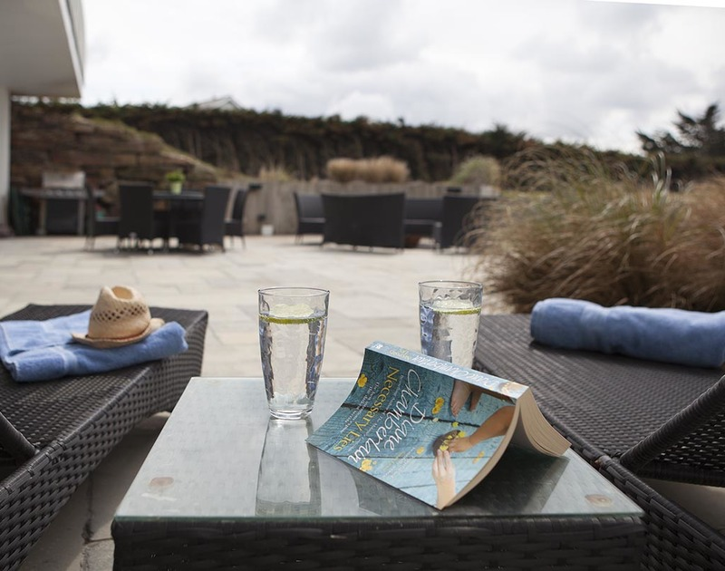 Relax and stretch out on a sun lounger on the terrace of Downalong, a magnificent holiday house at Daymer Bay, Cornwall,