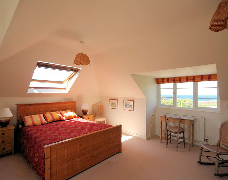Carpeted bedroom with large picture window and sea views in Cartway Cove in Port Gaverne, with a king sized bed and velux window.