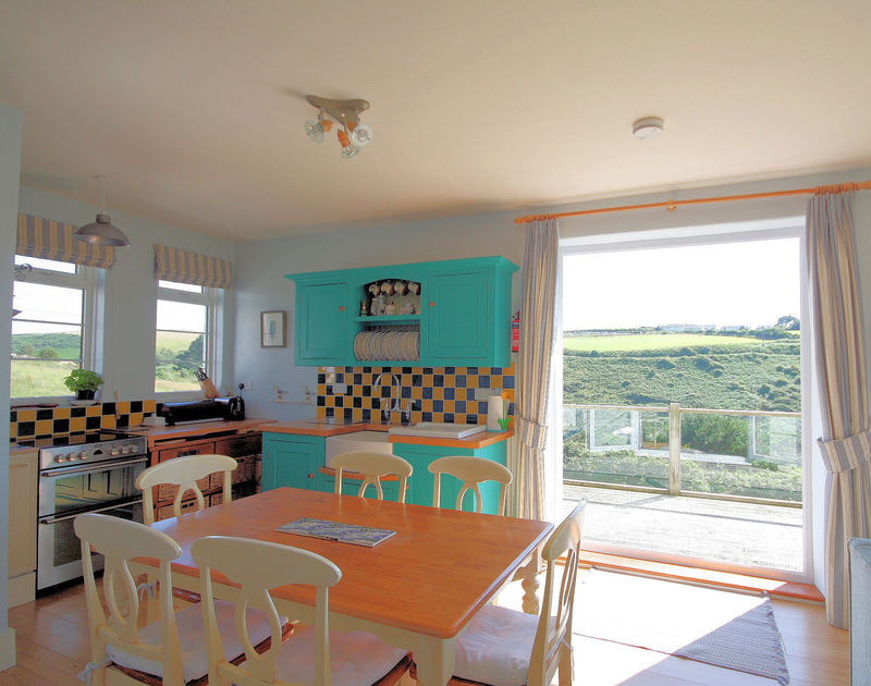 Rural views from the open plan kitchen dining area in Cartway Cove, Port Gaverne. Double doors lead on to the raised decking.