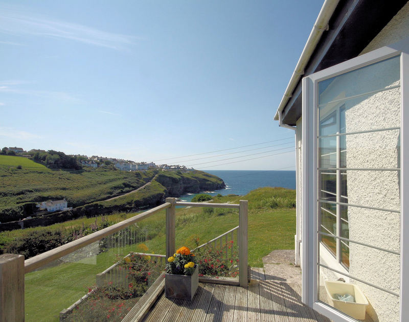 The view of the coastline and out to sea from the glass surrounded decked terrace with steps down to the lawned garden at Cartway Cove
