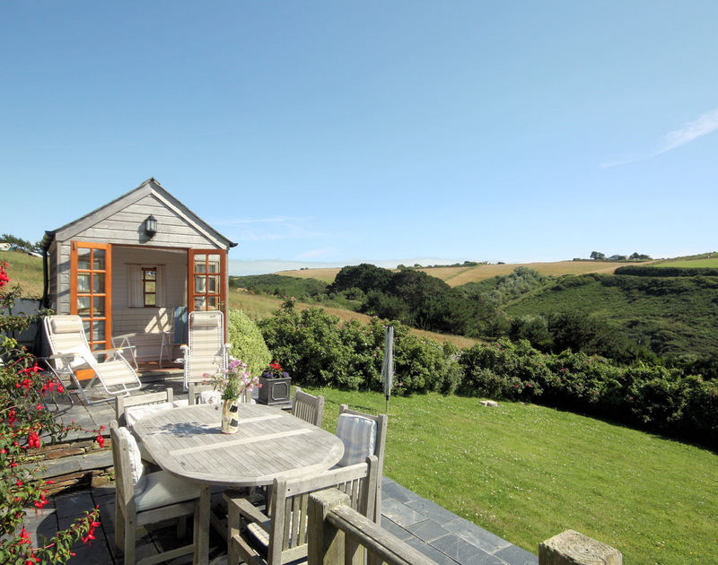 Lovely rural views and rolling lawned garden at Cartway Cove in Port Gaverne with slate patio and wooden summer house.
