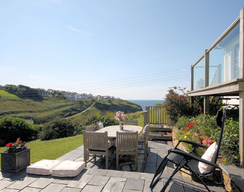 Outside slate patio dining area with stunning views towards Port Isaac, the coastline and out to sea from Cartway Cove, Port Gaverne