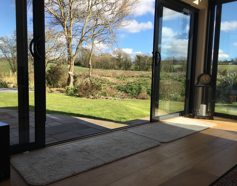 The large sliding glass doors onto the garden at Chy-An-Dowr, a self catering, pet friendly holiday rental in Rock, Cornwall.