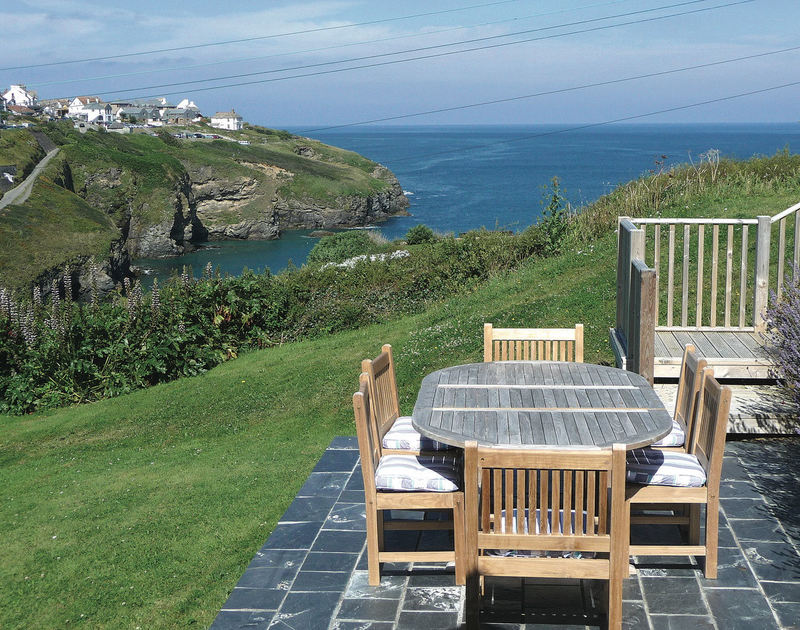 A lovely slate patio leading to the lawned garden at Cartway Cove in Port Gaverne with stunning views of the bay and out to sea.
