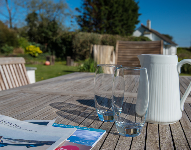 Space to read and enjoy a drink at the garden table in self catering holiday house, Tradewinds in Polzeath, Cornwall.