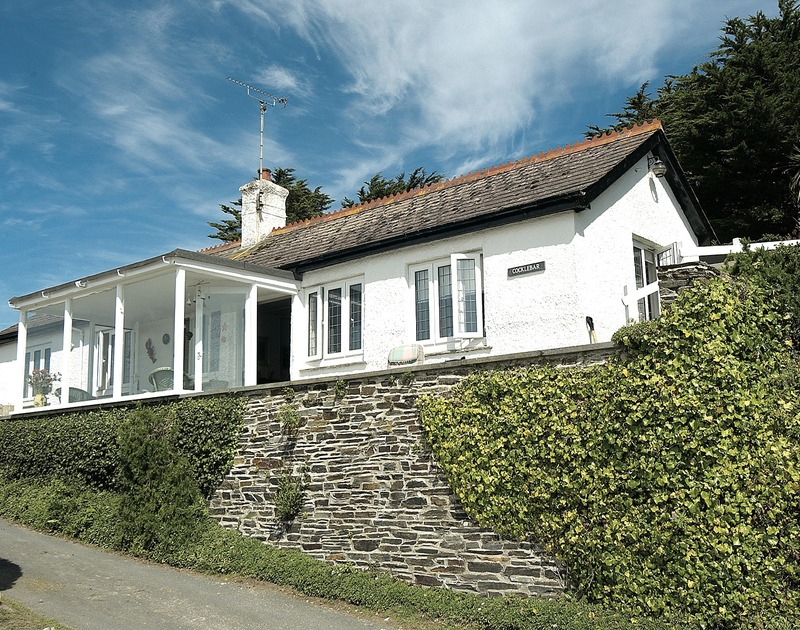 The exterior view of Cocklebar, a traditional holiday cottage to rent in Rock, Cornwall, showing its elevated position.
