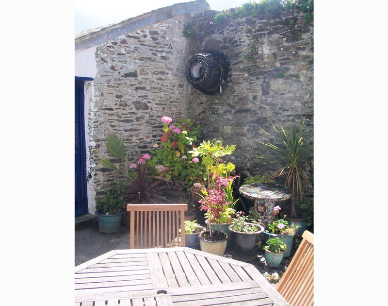 The sunny stone-walled courtyard of Quay Cottage, a holiday house in Port Isaac, with pretty planted containers.