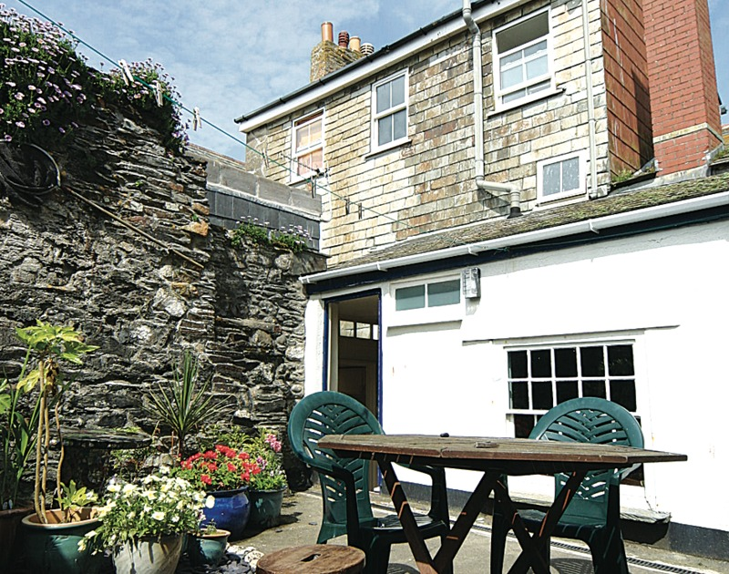 The rear of Quay Cottage, a holiday house in Port Isaac, Cornwall, with its sunny courtyard.