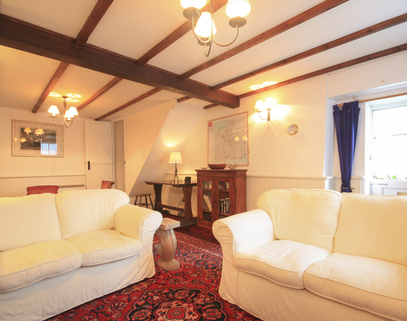 Two comfy sofas and elegant furnishings in the sitting room of Quay Cottage, a holiday house in Port Isaac, Cornwall