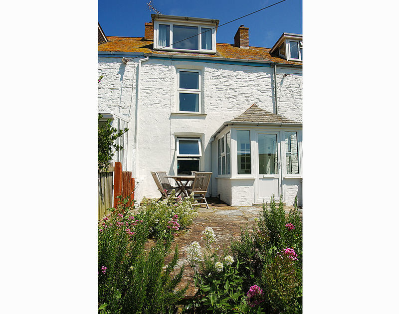The pretty garden and patio area outside at Tremanon, a self catering holiday cottage to rent in Port Isaac, Cornwall.