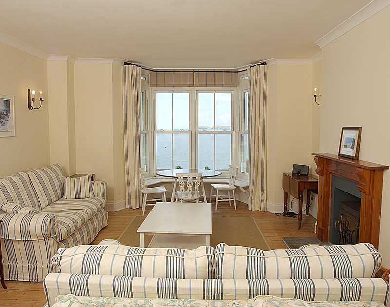 The lovely sitting room with far reaching sea and coastal views at Bellevue, a self catering holiday house above the beach at Port Gaverne, Port Isaac, Cornwall.
