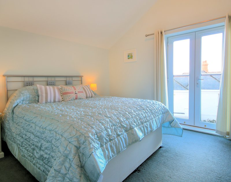 The master bedroom with kingsize bed and sea views at White Horses, a holiday rental in Port Isaac, Cornwall