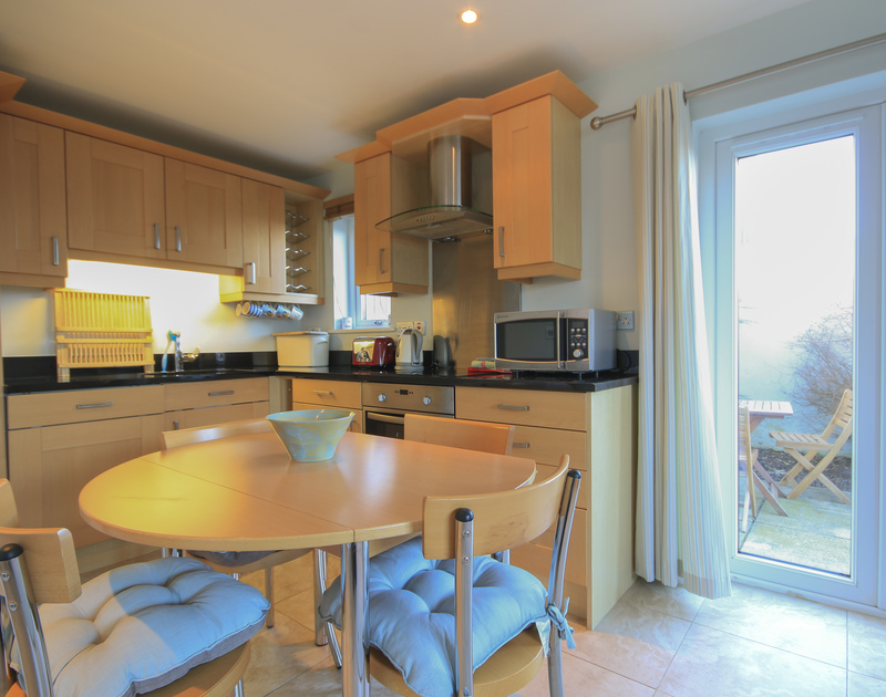 The well-equipped kitchen/diner at White Horses, a holiday house in Port isaac, Cornwall, with door to the patio.