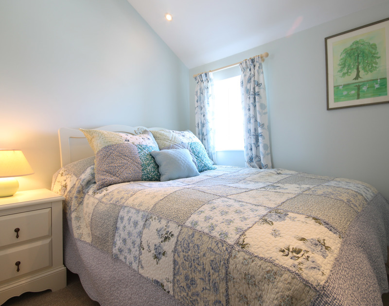 Cosy bedroom at White Horses, a holiday house in Port Isaac, Cornwall, with lovely quilted bedspread and cushions.