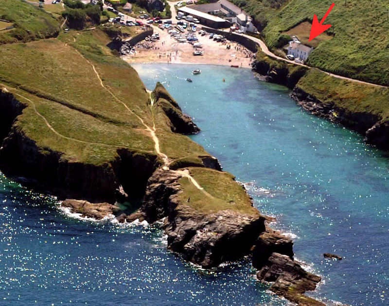 Aerial view of the stunning coastal location of Rockies, a holiday house perched above Port Gaverne, near Port Isaac, Cornwall