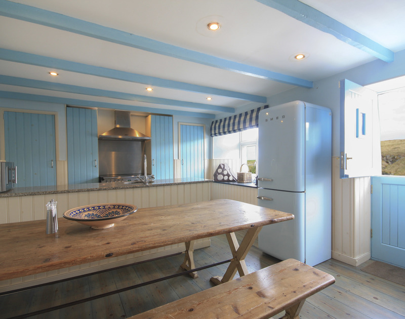 The attractive blue and cream kitchen at Rockies, a holiday house in Port Isaac, with large table and benches.