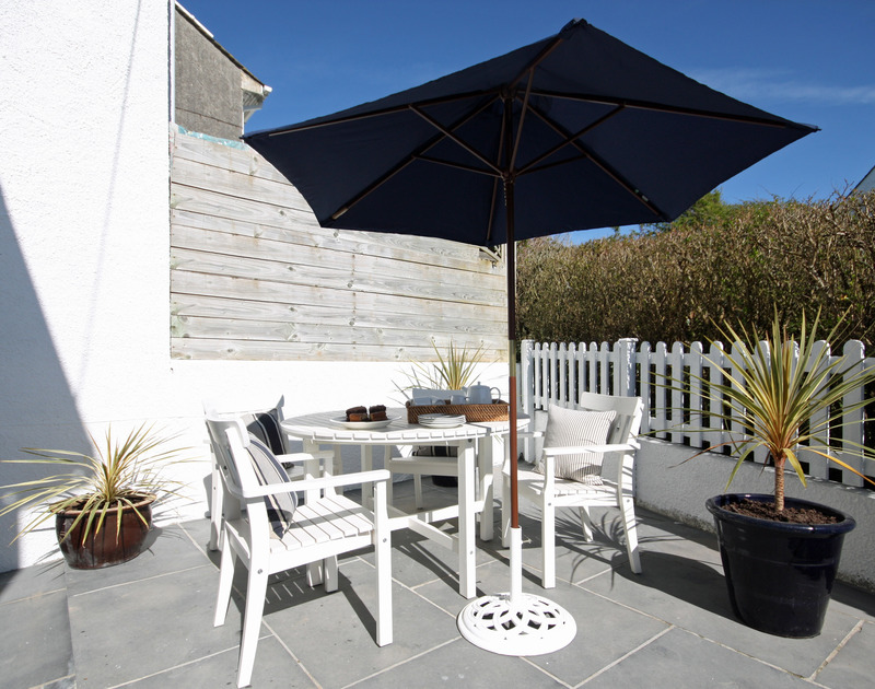 The sunny, sheltered terrace with garden furniture at Castaway, a ideally located seaside holiday rental at Port Isaac in North Cornwall.