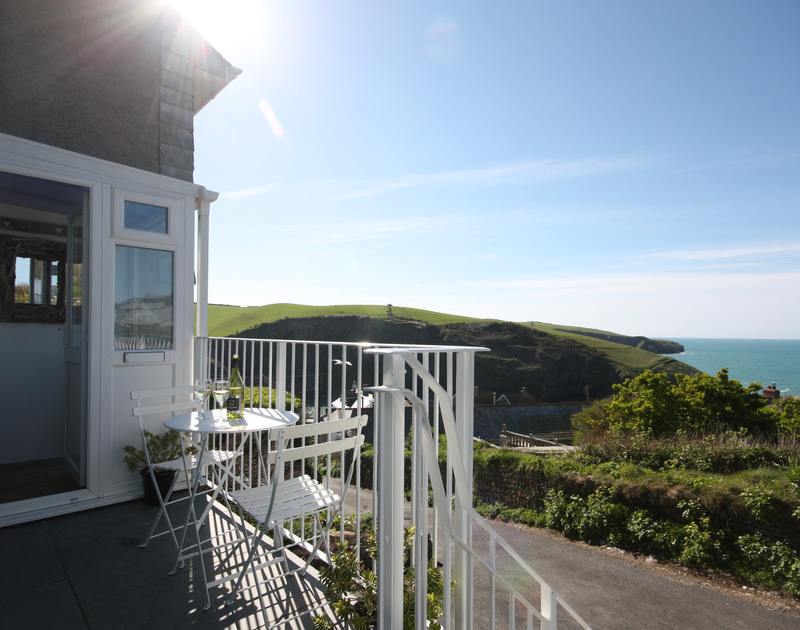 The sunny patio with beautiful coastal views at Castaway, a self catering holiday rental in Port Isaac, Cornwall.