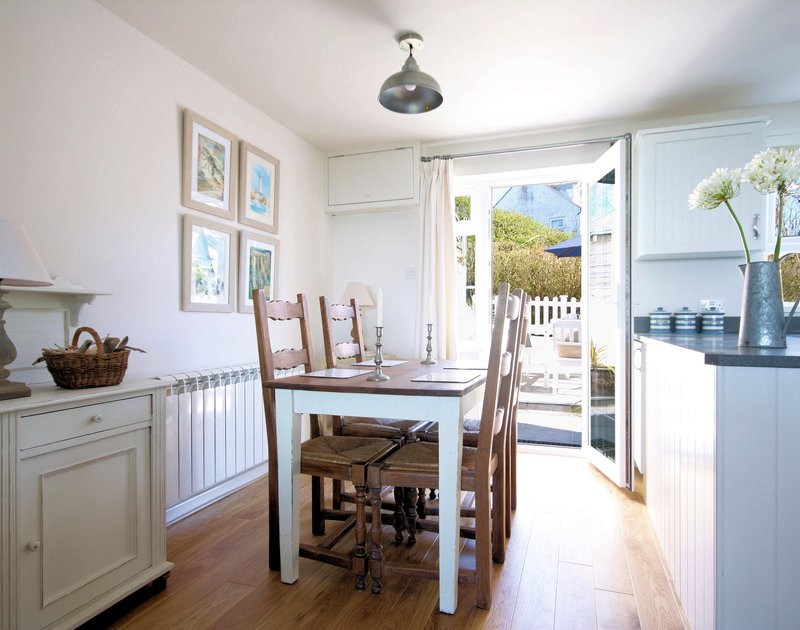 Elegant dining table in the open plan kitchen/diner at Castaway,  a luxurious self catering holiday retreat ideal for a small family or a romantic couple in Port Isaac, Cornwall.