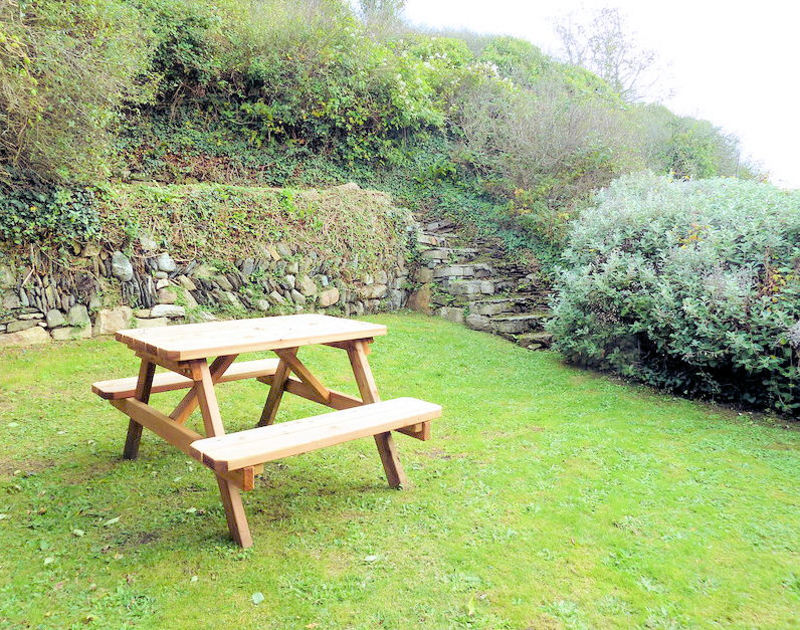 A picnic table in the garden with slate steps at The Cobweb, a self catering holiday rental in Port Isaac, North Cornwall.