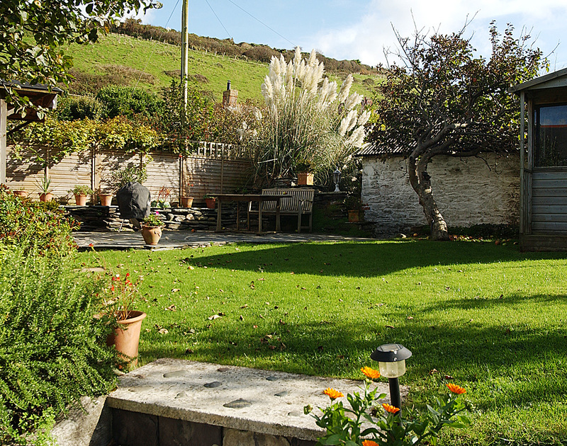 The level, lawned garden of Brook Cottage, a holiday house near the harbour of Port Isaac, Cornwall.