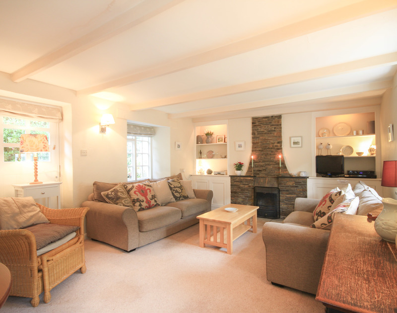 Beautifully furnished sitting room at Brook Cottage, a holiday cottage in Port Isaac, Cornwall with open fire place.