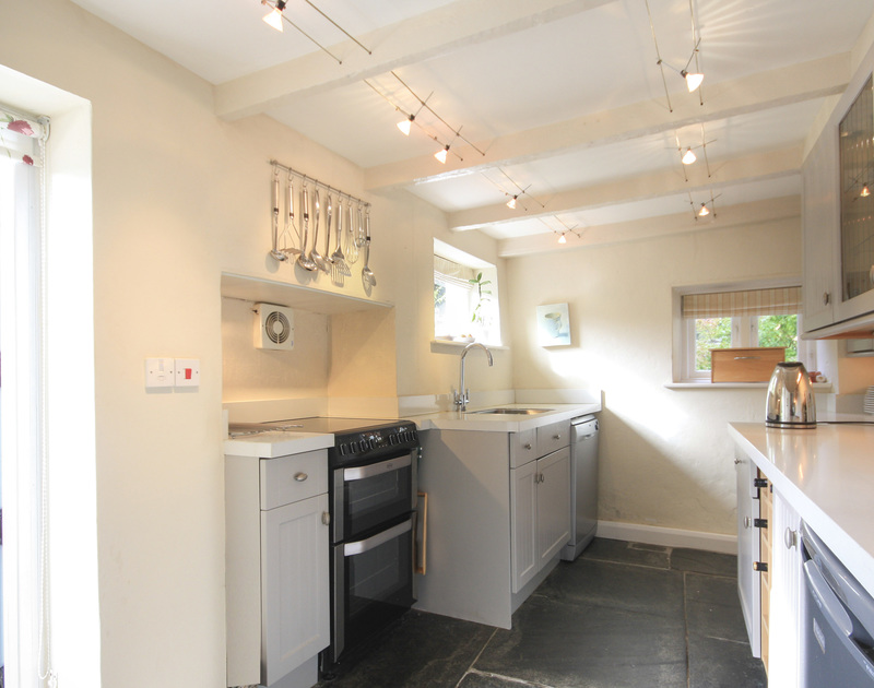 Stylish kitchen at Brook Cottage, a self-catering holiday cottage in Port Isaac, Cornwall, with slate flagstone floor.