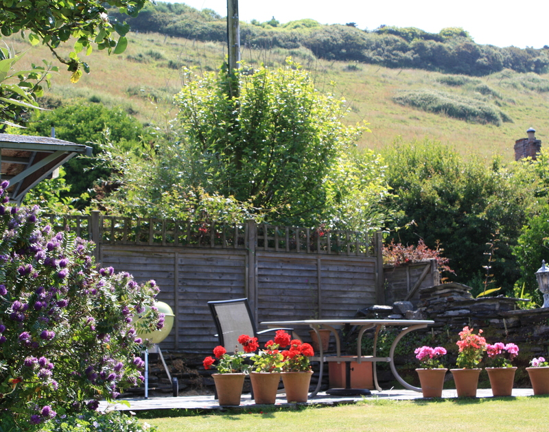 The patio area of Brook Cottage, a holiday house in Port Isaac, Cornwall, with garden furniture.