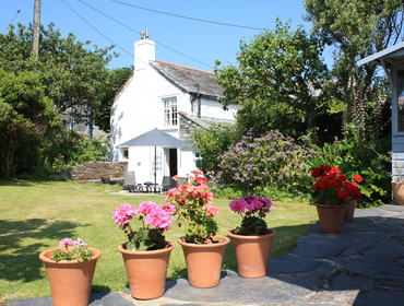 The lawned garden and side view of Brook Cottage, a charming holiday cottage in Port Isaac, Cornwall
