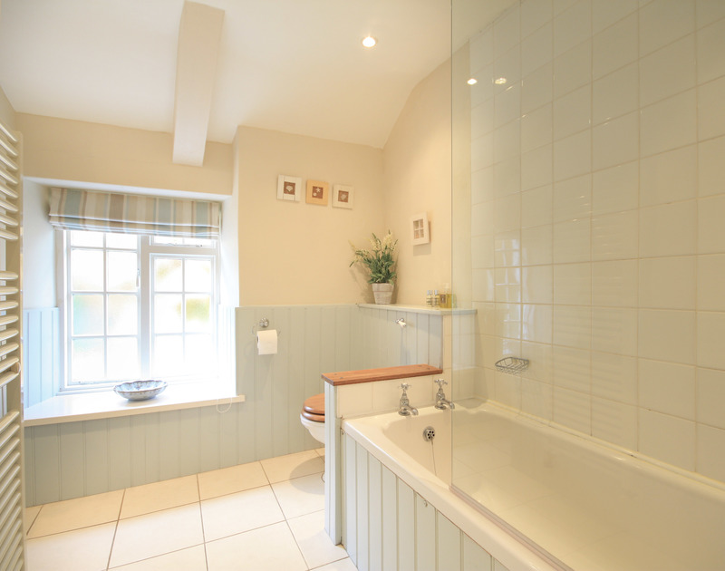 Smart, fresh bathroom at Brook Cottage, a holiday cottage in Port Isaac, with bay window and painted wall panelling.