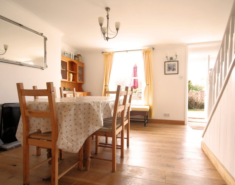 The spacious dining room of Morwenna, a holiday house in Port Isaac, Cornwall, with lovely wooden floor.