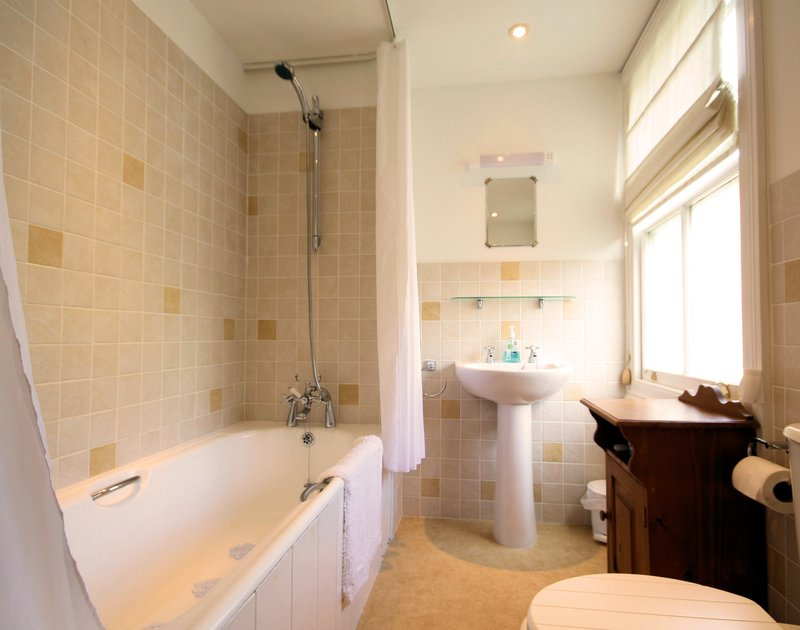 The family bathroom of Morwenna, a holiday house in Port Isaac, Cornwall, with shower attachment over the bath.