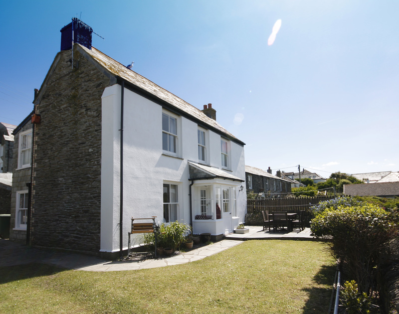 The exterior view of Morwenna, a self-catering, characterful holiday house in Port Isaac, Cornwall, with lawned garden and terrace.
