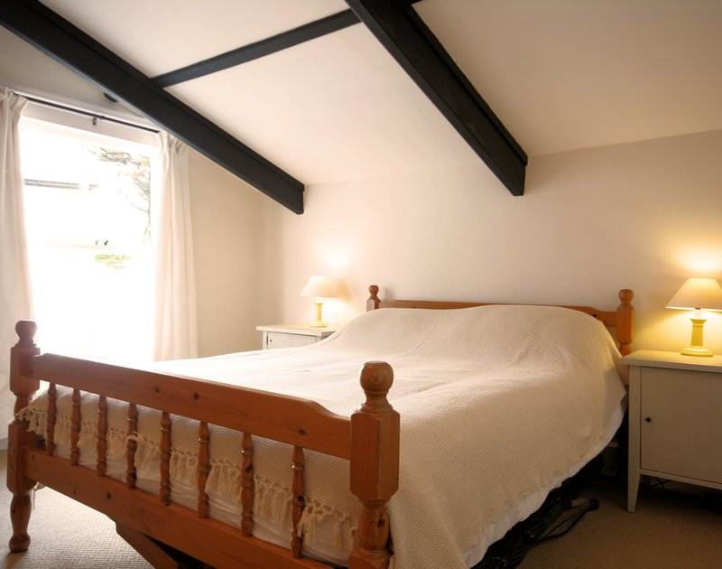 Double bedroom at Morwenna, a holiday house in Port Isaac, Cornwall, with sloping beamed ceiling.