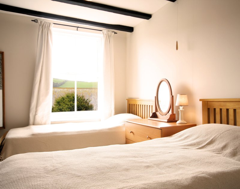 The twin bedroom at Morwenna, a holiday house in Port Isaac, Cornwall, with large window allowing valley views.