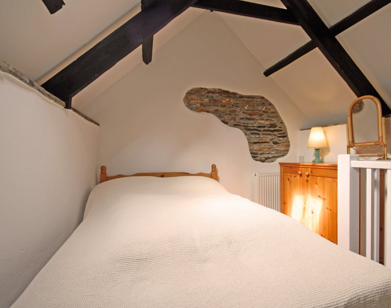 Cosy, characterful double bedroom at Morwenna, a holiday house in Port Isaac, Cornwall, with stone work detail.
