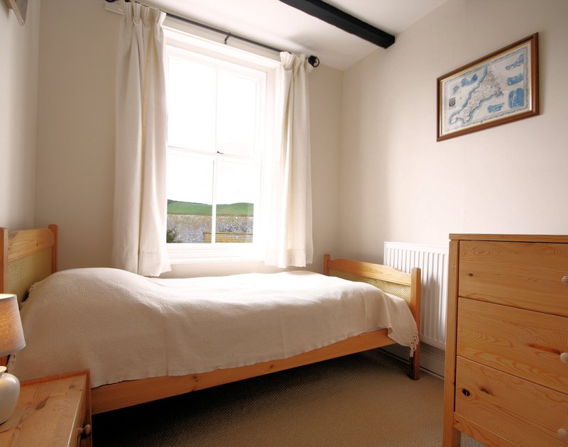 The single bedroom at Morwenna, a holiday house in Port Isaac, Cornwall, with large sash window.