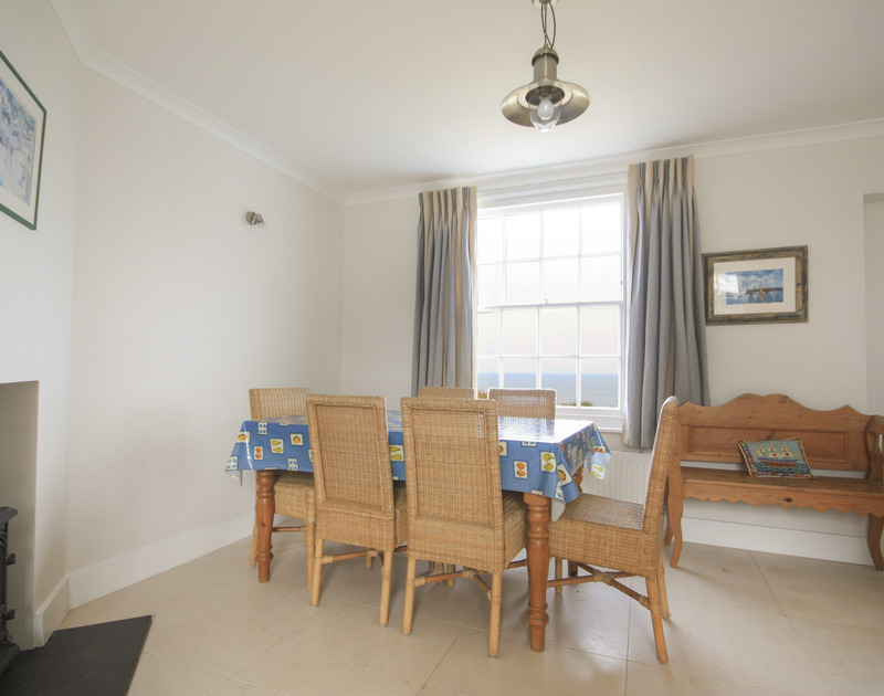 The dining table in the window with uninterrupted sea views at Coastguard Cottage 3, a self catering holiday house to rent on the clifftop above Port Isaac in North Cornwall.