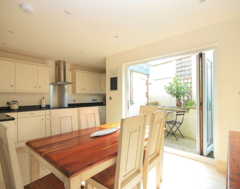 The smart kitchen of Seaspray, a holiday rental in Port Isaac, Cornwall, with bifold doors to a small courtyard.