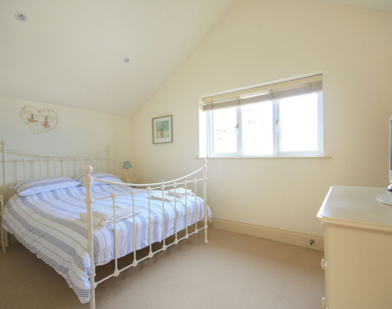 Light, double bedroom of Seaspray, a holiday house in Port Isaac, Cornwall, with ornamental bedstead.