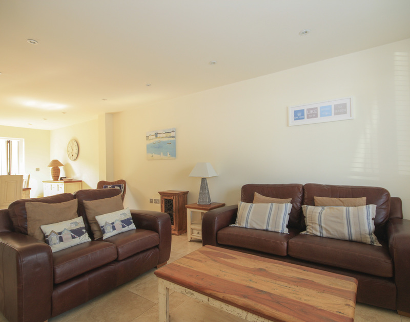 The comfy sitting room of Seaspray, a holiday house in Port Isaac, Cornwall, with two matching sofas and a large coffee table.