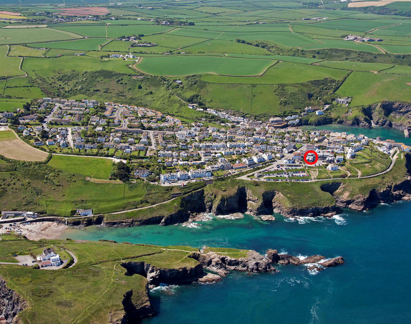A high aerial view of the cliffside location of Seaspray, a holiday house in Port Isaac, Cornwall, with Port Gavern cove in the foreground.
