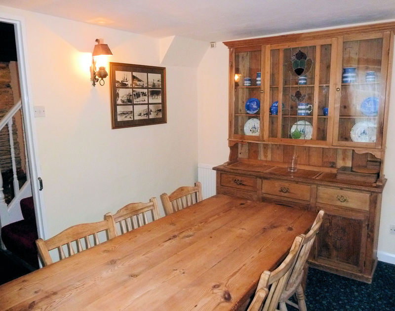 The good sized dining table and attractive dresser in the dining room at Mermaid Cottage, a self catering holiday rental in Port Isaac, Cornwall.