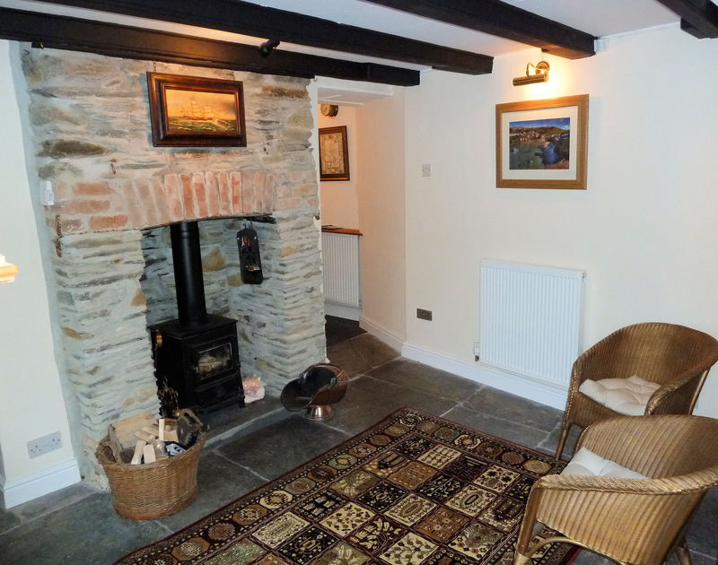 The charming and welcoming woodburner and the original slate floored entrance hall at Mermaid Cottage, a self catering holiday rental in Port Isaac, Cornwall.